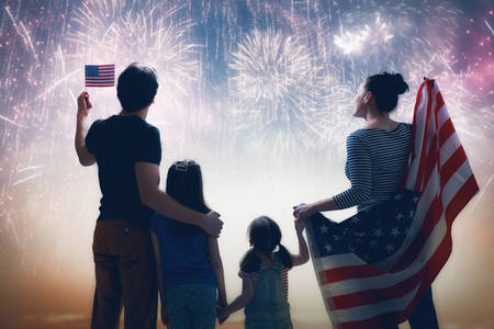 Patriotic holiday. Happy family, parents and daughter child girl with American flag outdoors. USA celebrate 4th of July. 版權商用圖片 - 123954408