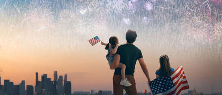 Patriotic holiday. Children and father holding the Flag of the USA. America celebrate 4th of July.