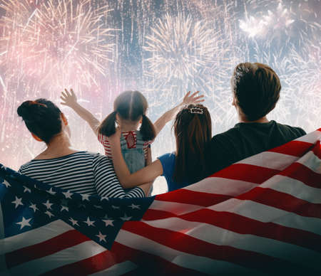 Patriotic holiday. Happy family, parents and daughter child girl with American flag outdoors. USA celebrate 4th of July. Stock Photo