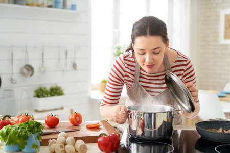 Alimentation saine à la maison. Une femme heureuse prépare le bon repas dans la cuisine. Banque d'images