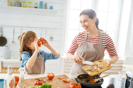 Healthy food at home. Happy family in the kitchen. Mother and child daughter are preparing proper meal.