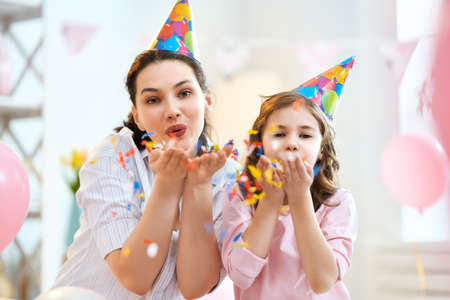 Funny time. Mom and her child daughter are playing at home. Girls are throwing confetti. Family holiday and togetherness. Stock fotó