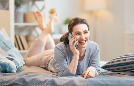 Happy casual beautiful woman is talking on a phone sitting on the bed in the house. Stock fotó