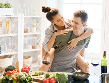 Healthy food at home. Happy loving couple is preparing the proper meal in the kitchen. Stock Photo
