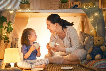 Gelukkig liefdevol gezin. Moeder en haar dochtermeisje spelen theekransje en drinken thee uit kopjes in de kinderkamer. Grappige moeder en mooi kind plezier binnenshuis.