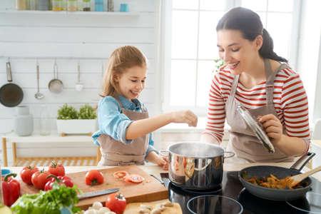 Gesundes Essen zu Hause. Glückliche Familie in der Küche. Mutter und Tochter bereiten richtige Mahlzeit zu. Standard-Bild