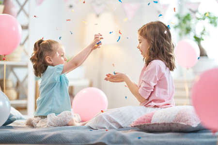 Funny time. Children are playing at home. Girls are throwing confetti. Family holiday and togetherness. Stock fotó