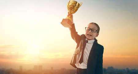 Little child is winner. Kid on sunset background. Smart power concept. The Cup for first place. Stock fotó