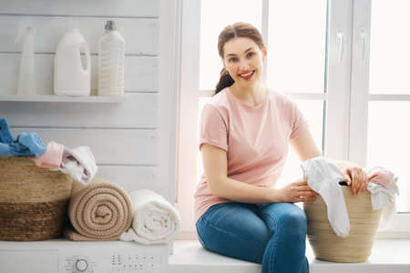 Beautiful young woman is smiling while doing laundry at home. Reklamní fotografie