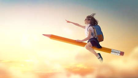 Zurück zur Schule! Glückliches süßes fleißiges Kind, das auf dem Bleistift auf dem Hintergrund des Sonnenunterganghimmels fliegt. Konzept der Bildung und des Lesens. Die Entwicklung der Vorstellungskraft.