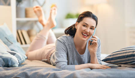 Happy casual beautiful woman is talking on a phone sitting on the bed in the house.