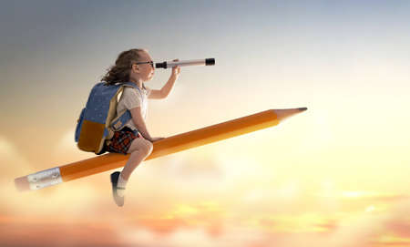 Zurück zur Schule! Glückliches süßes fleißiges Kind, das auf dem Bleistift auf dem Hintergrund des Sonnenunterganghimmels fliegt. Konzept der Bildung und des Lesens. Die Entwicklung der Vorstellungskraft. Standard-Bild