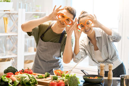 Healthy food at home. Happy loving couple is preparing the proper meal in the kitchen. Stock fotó