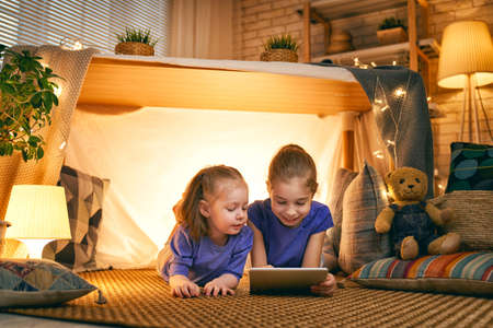Cute little children are playing with tablet in tent. Happy girls at home. Funny lovely kids having fun in room. Stock fotó