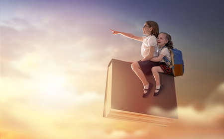 Back to school! Happy cute industrious children are flying on the book on background of sunset sky. Concept of education and reading. The development of the imagination. Stock fotó