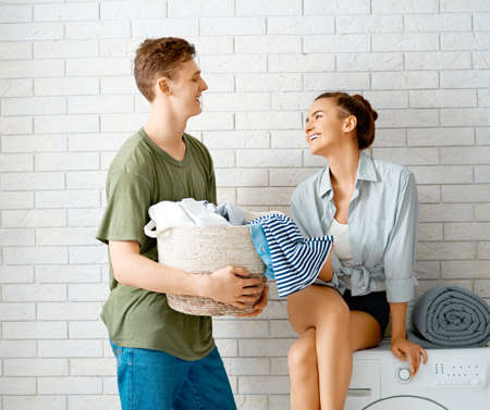 Beautiful young loving couple is smiling while doing laundry at home.