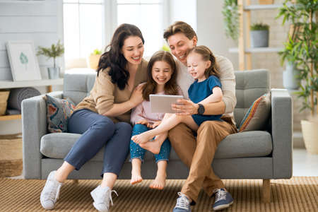 Happy loving family. Young mother, father and their daughters girls playing at home. Funny mom, dad and lovely children are having fun with tablet.