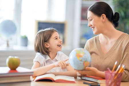 Back to school. Happy child is sitting at desk. Girl with teacher in classroom. Stock Photo