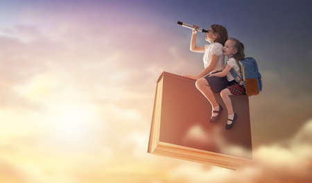 Back to school! Happy cute industrious children are flying on the book on background of sunset sky.