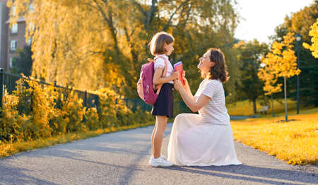 Parent and pupil of primary school go hand in hand. Woman and girl with backpack behind back. Beginning of lessons. First day of fall. Standard-Bild