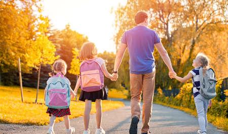 Parents et élèves du primaire vont de pair. Homme et filles avec des sacs à dos derrière le dos. Début des cours. Premier jour d'automne. Banque d'images