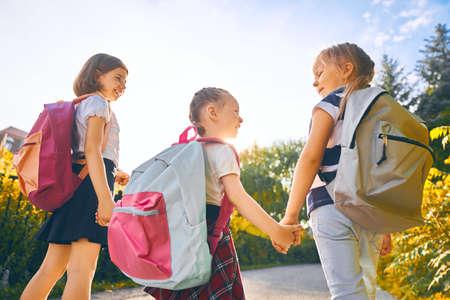 Uczniowie szkoły podstawowej. Dziewczyny z plecakami na zewnątrz. Początek lekcji. Pierwszy dzień jesieni.