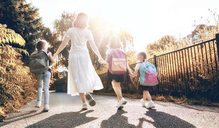 Femme et filles avec des sacs à dos derrière le dos. Début des cours. Premier jour d'automne. Banque d'images