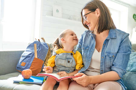 happy loving family. pretty young mother and her daughter are writing in notebook. Stock Photo - 129045200
