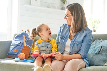 happy loving family. pretty young mother and her daughter are writing in notebook. Stock Photo - 129045331