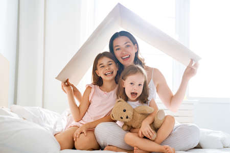 Mother and children girls in the room with a symbol of roof. Concept of housing for young family. Stock Photo