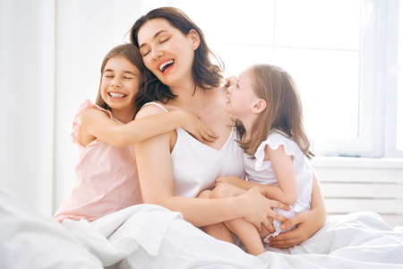 A nice girls and their mother enjoy sunny morning. Good time at home. Children waking up from sleep. Family playing on the bed in the bedroom. Stock Photo