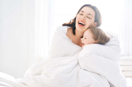 A nice girl and her mother enjoy sunny morning. Good time at home. Child wakes up from sleep. Family playing on the bed in the bedroom.