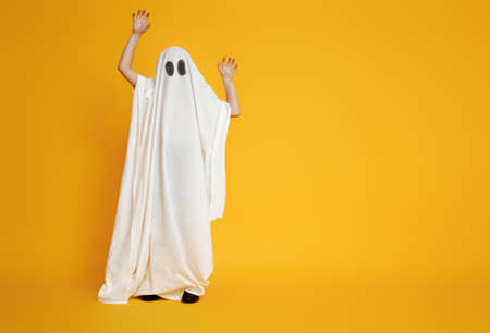 Happy Halloween! Cute little kid in ghost costume on yellow background.