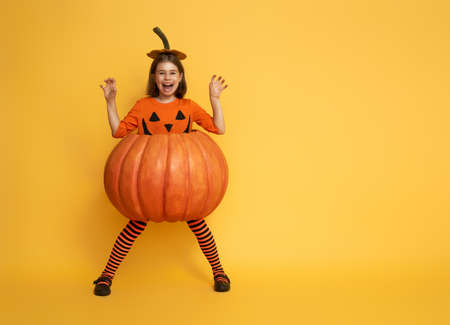 Happy Halloween! Cute little girl in pumpkin costume on yellow background. Stockfoto