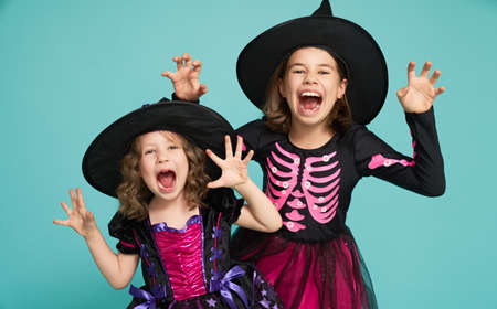 Happy Halloween! Cute little witches on turquoise background.