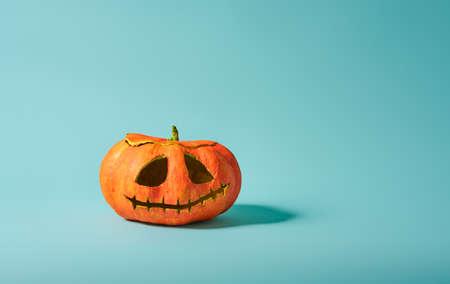 Happy halloween! Pumpkin lantern on turquoise background.