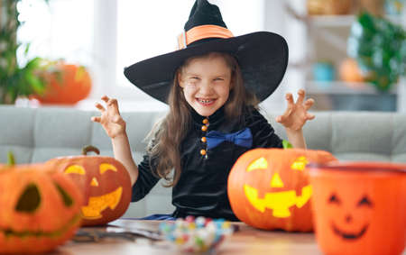 Happy Halloween! Cute little laughing girl in witch costume with a pumpkin. Stockfoto
