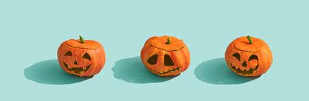 Happy halloween! Pumpkins lanterns on turquoise background.