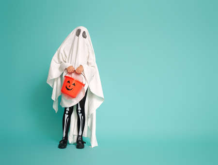 Happy Halloween! Cute little kid in ghost costume on teal background.