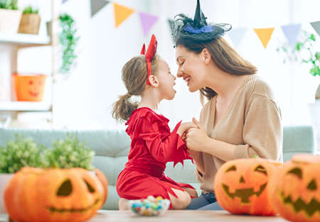 Mother and her daughter having fun at home. Happy Family preparing for Halloween.