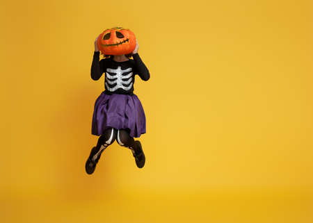 Happy Halloween! Cute little girl in skeleton costume with pumpkin on yellow background. Фото со стока