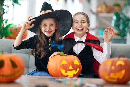 Cute little children girls with carving pumpkin. Happy family preparing for Halloween.