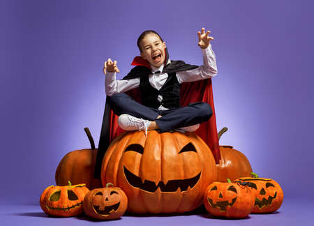 Happy Halloween! Cute little Dracula with a pumpkin on purple Foto de archivo - 129603333