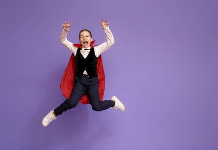 Happy Halloween! Cute little Dracula on purple