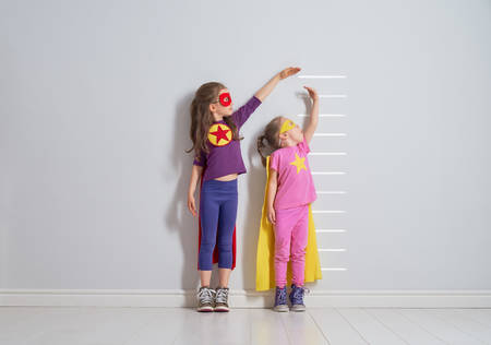 Two little children are playing superhero. Kids are measuring the growth on the background of wall. Girl power concept. Archivio Fotografico