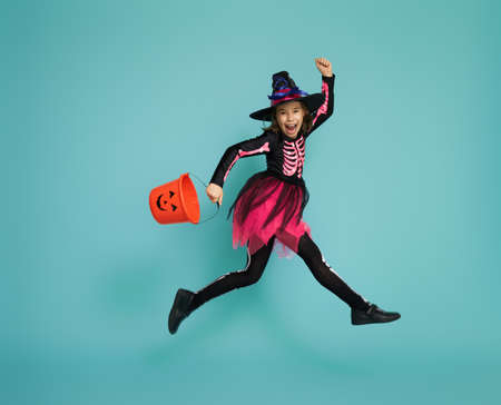 Happy Halloween! Cute little witch with a basket on turquoise background.