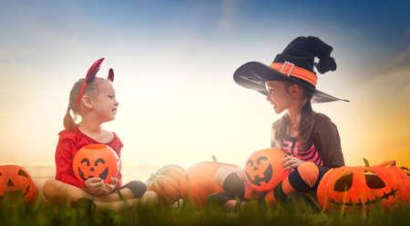 Chicas felices en Halloween. Niños divertidos en disfraces de carnaval al aire libre. Niños alegres y calabazas en el fondo del atardecer. Foto de archivo