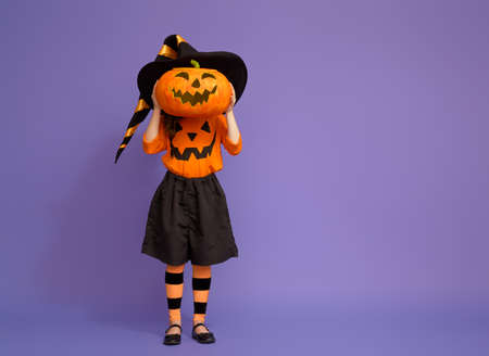 Happy Halloween! Cute little witch with a pumpkin on violet background. Imagens