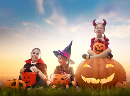 Happy girls on Halloween. Funny kids in carnival costumes outdoors. Cheerful children and pumpkins on sunset background. Imagens