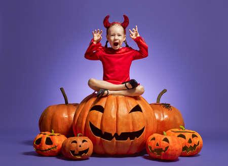 Happy Halloween! Cute little devil with pumpkins on violet background.